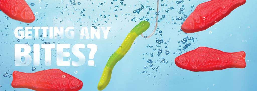 """Advertising Concept called """"Getting Any Bites"""" underwater with Swedish fish in bubbles next to a green gummy worm on a fishing hook"""