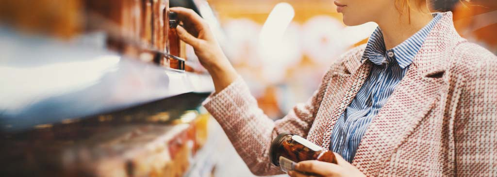 A Business Woman standing in a supermarket at a shelf inspecting products